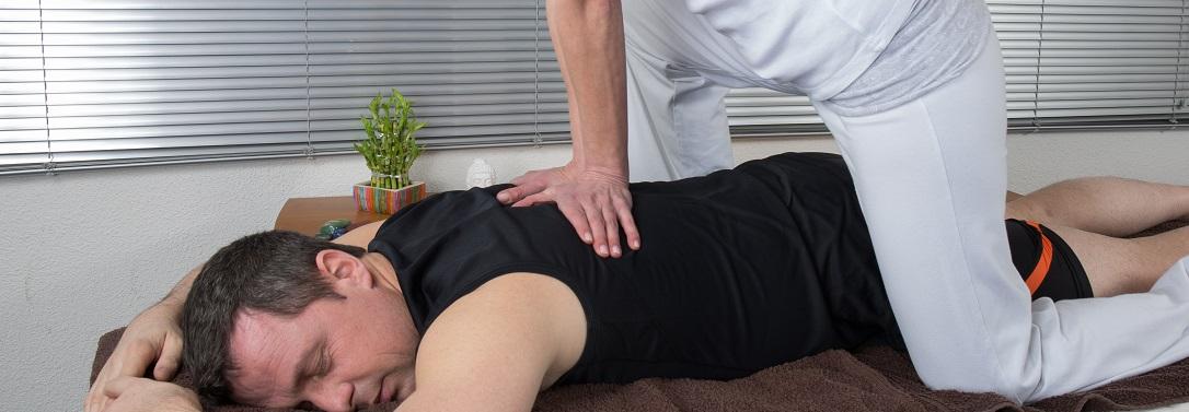 One man and woman performing back shiatsu massage